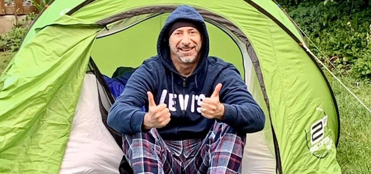 man sat in green tent with thumbs up, wearing a blue hooded top and checked trousers