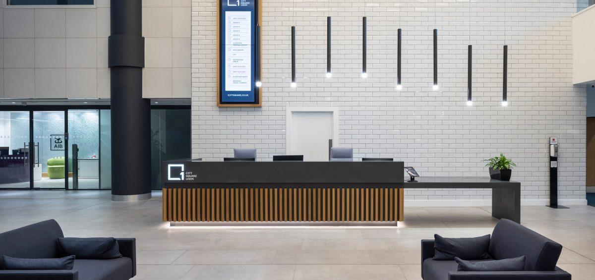 interior of a company reception area, with desk and black sofas